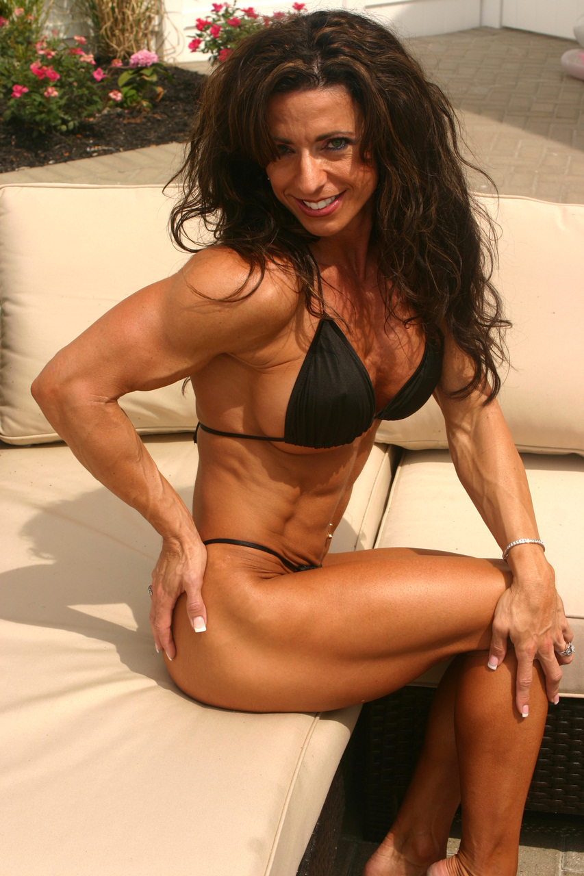 Mature Woman Exercising Biceps On Cable Machine In The Gym And Flexing Muscles