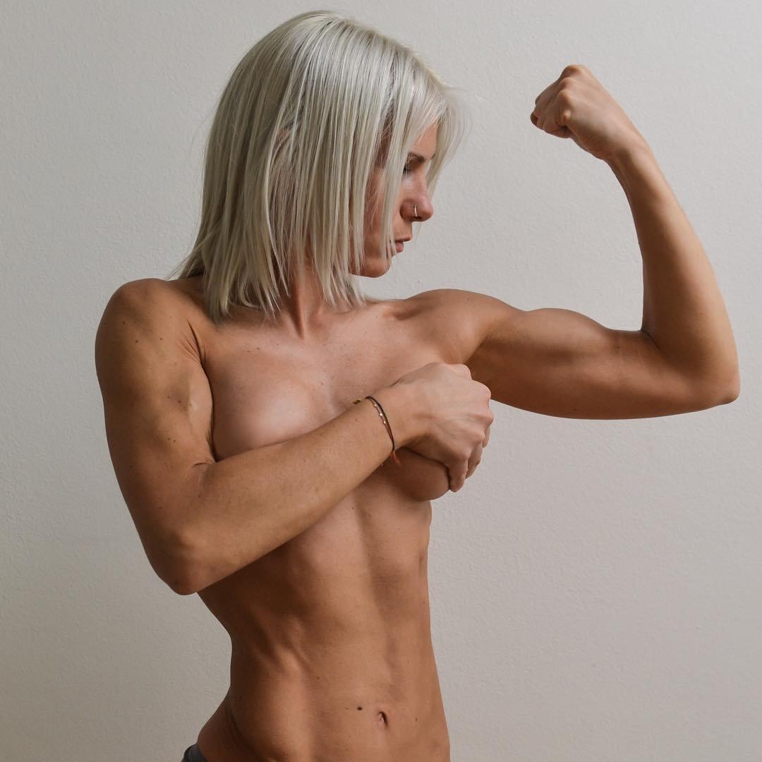 Female bodybuilder flexing big biceps by female bodybuilder